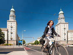Cyclist rides past Frankfurter Tor apartment buildings on historic Karl Marx Allee in former East Berlin in Berlin, Germany