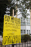 An individual is selling their flat privately for £10,000 + cash on the A202 Peckham Road. Without using an established high street estate agent (realtor) the owner called Nathan has left his own sign attached to railings outside a block of flats on this main road between Camberwell and Peckham in south London. He describes the property as a 2 bed apartment and unusually for London, complete with garage space.