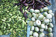 Cucumbers and eggplant/aubergines for sale at Daeum Kor morning market in Phnom Penh, the capital city of Cambodia. A large variety of local products are available for sale in fresh markets all over Cambodia, all being sold on small individual stalls.