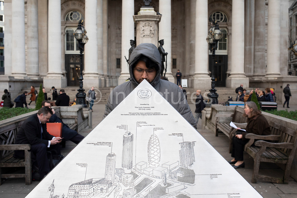 Man looks at the triangular map in the space known as Bank Triangle in the City of London on 28th January 2020 in London, England, United Kingdom. The City of London is a historic financial district, home to both the great banking buildings. Modern corporate skyscrapers tower above the vestiges of medieval alleyways below.