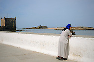 Morocco, Essaouira. Moroccan man looking at the see.