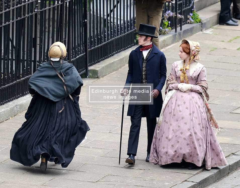 """Moray Place in Edinburgh's Georgian old town was turned into 19th century London for Julian Fellowes' new ITV show """"Belgravia"""".<br /> <br /> Pictured: An actress dressed as a maid checks her boots are laced up correctly but has to make some adjustments before she runs along the street.<br /> <br /> Alex Todd   Edinburgh Elite media"""