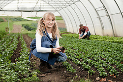 Smiling blond girl in greenhouse