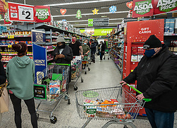 © Licensed to London News Pictures. 21/12/2020. London, UK. Chaotic scenes at Asda in Wandsworth, South West London as a huge rush of shoppers descended on the store causing long queues in the aisles after news that French customs blocked freight from leaving Dover to France after a Covid-19 mutation caused a rapid increase of infection throughout the capital and South East of England. Last week Prime Minister Boris Johnson put London and parts of the South East into Tier 4 lockdown after the new Covid-19 mutation was discovered. Photo credit: Alex Lentati/LNP