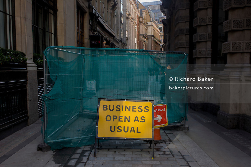 A sign saying that Business Open As Usual stands in a narrow City of London street.