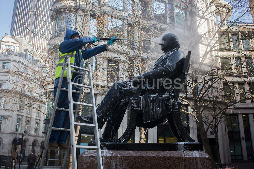 A conservator with City of London contractor Rupert Harris Conservation, uses a pressure jet spray to hose off  urban grime the statue of Victorian philanthropist, entrepreneur and banker George Peabody (1795 to 1869). As part of a rolling programme of maintenance and cleaning by the Square Mile's governing Corporation, historic items - from statues and plaques to other pieces of historic value are regularly attended to.