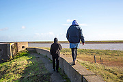 Mother and adult son walking on a low wall together by the River Ore, Suffolk, England, UK