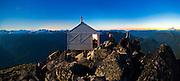 Stephen Byrne watches the sunset from the fire lookout cabin on the summit of Hidden Lake Peaks, North Cascades National Park, Washington.