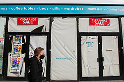 © Licensed to London News Pictures. 19/10/2020. London, UK. A woman wearing a face covering in north London walks past a store which has closed due to coronavirus crisis. According to the figures, revealed by the Local Data Company and advisory firm PricewaterhouseCoopers (PwC), a total of 11,120 shops on UK high streets closed in the first half of this year due to the coronavirus lockdown.  Photo credit: Dinendra Haria/LNP