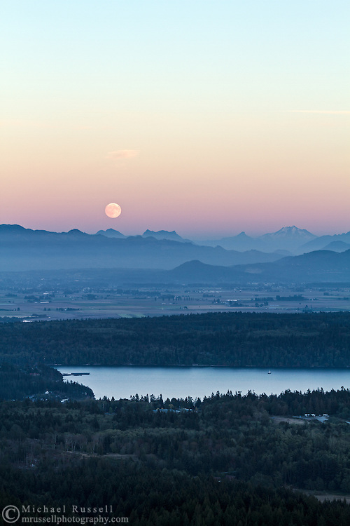 The moon rises into the Belt of Venus over the peaks of the North Cascades mountains in Washington State, USA.  Peaks here include (L to R) Round Mountain, Mount Higgins, Skadulgwas Peak, White Chuck Mountain, Glacier Peak, Disappointment Peak and Whitehorse Mountain.  Similk Bay is in the foreground. Photographed from Mt. Erie Park on Fidalgo Island, Washington.