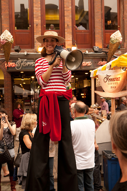 New York, NY -24 September 2011. The feast of San Gennaro in New York's Little Italy. A woman on stilts, wearing a gondolier's outfit, enticing bystanders into the Ferrara coffee bar.