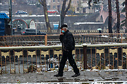 A man wearing a face surgical protective mask walks through the bridge over the Voghji River in the city centre of Kapan, Syunik Province in Southern Armenia on Friday, Dec 18, 2020. Armenia didn't establish Covid19 wards across the country and didn't manage to establish restriction measures to curb the spread of coronavirus pandemic outbreak due to an escalated 44 days of the war with Azerbaijan. Most of the people appear to not wearing face protective masks or apply social distancing across the country. Kapan is a provincial capital of Syunik Province in southeast Armenia. It is located in the valley of the Voghji River and is on the northern slopes of Mount Khustup. Kapan lays along the disputed borderline with Azerbaijan with whom Armenia's long-standing frozen conflict escalated into a full scare of war for the 3rd time on Sept 27, 2020. (Photo/ Vudi Xhymshiti)