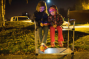 Kinsey Pietrasik, 12 (left), and Keanna Camero, 4, watch cartoons on a mobile device during a Milpitas Food Pantry event at Lifegate Church in Milpitas, California, on November 25, 2013. (Stan Olszewski/SOSKIphoto)