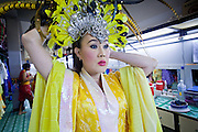 """Oct. 7, 2009 -- BANGKOK, THAILAND:  A """"ladyboy"""" adjusts her headpiece before going on stage at the Mambo Cabaret in Bangkok, Thailand. The performers at the Mambo Cabaret in Bangkok, Thailand are all """"Ladyboys,"""" or kathoeys in Thai. Recognized as a third gender, between male and female, they are born biologically male but live their lives as women. Many kathoey realize they are third gender in their early teens, some only as old 12 or 13. Kathoeys frequently undergo gender reassignment surgery to become women. Being a kathoey in Thailand does not carry the same negative connotation that being a transgendered person in the West does. A number of prominent Thai entertainers are kathoeys. Photo by Jack Kurtz / ZUMA Press"""
