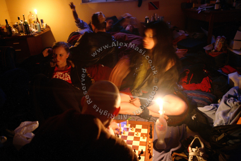 Some squatters and other friends are staying in the same room to keep warm after having ran out of petrol for their generator on Sunday, Oct. 7, 2007, in the Ingram Avenue mansion, Hampstead, London, England. Some of them are playing chess at candlelight, while others are just relaxing on the bed after a party has been going on the night before. The 22-room mansion was last sold for UK£ 3.9M in 2002 and is now awaiting planning permissions to be demolished. Two new houses will soon be taking its place. Million Dollar Squatters is a documentary project in the lives of a peculiar group of squatters residing in three multi-million mansions in one of the classiest residential neighbourhoods of London, Hampstead Garden. The squatters' enthusiasm, their constant efforts to look after what has become their home, their ingenuity and adventurous spirit have all inspired me throughout the days and nights spent at their side. Between the fantasy world of exclusive Britain and the reality of squatting in London, I have been a witness to their unique story. While more than 100.000 properties in London still lay empty to this day, squatting provides a valid, and lawful alternative to paying Europe's most expensive rent prices, as well as offering the challenge of an adventurous lifestyle in the capital.