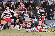 Adam Warren of the Newport Gwent Dragons charges forward as Stuart Mcinally of Edinburgh rugby hangs on by his finger tips. Guinness Pro12 rugby match, Newport Gwent Dragons v Edinburgh Rugby at Rodney Parade in Newport, South Wales on Sunday 27th March 2016.<br /> pic by  Simon Latham, Andrew Orchard sports photography.