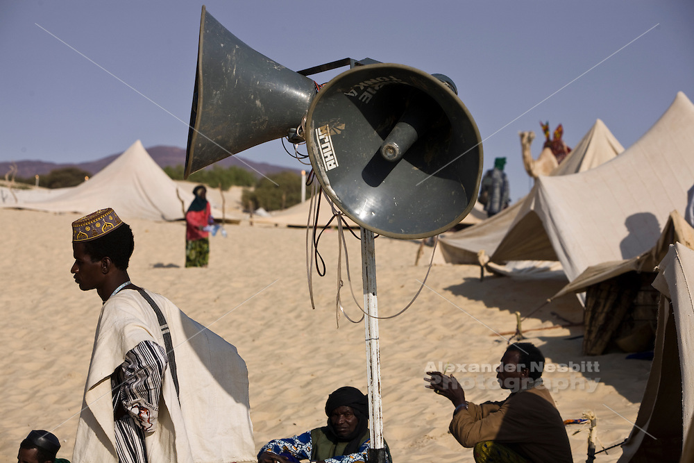 Essakane, Mali, 2009 -  At the Festival au Desert in Mali. Men relax on the sand near their tents under a large primitive PA speaker. The festival is held in an open desert area with no facilities or infrastructure and all equipment, like the loudspeakers, needs to be trucked in.