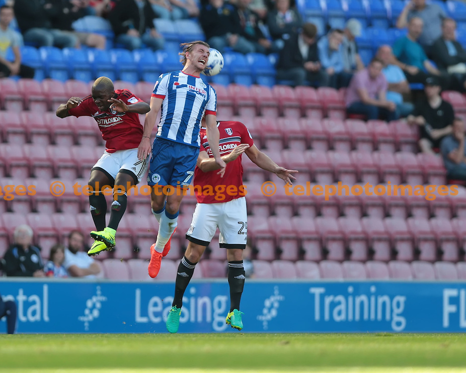 Wigan Athletic midfielder Alex Gilbey (7) heads the ball under pressure during the Sky Bet Championship match between Wigan Athletic and Fulham at the DW Stadium in Wigan. September 17, 2016.<br /> Nigel Pitts-Drake / Telephoto Images<br /> +44 7967 642437