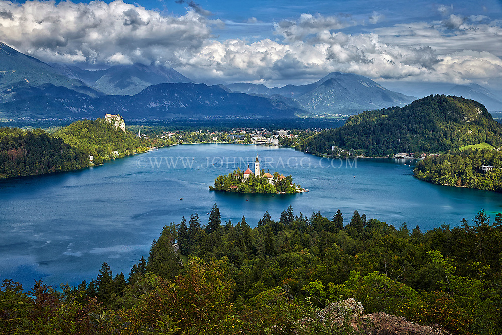 Lake Bled in Slovenia has a small island in the center and is surrounded by the Julian Alps in the background.