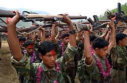 "RUKUM DISTRICT, NEPAL, APRIL 22, 2004:  A battalion of Maoist insurgents gather in Rukum district April 22, 2004 weeks after their attack on government troops in Beni when they overran the district headquarters, looting a bank, destroying the jail and torching government office buildings. The government said that 32 security personnel died in the clash and 37 were kidnapped. The clash was one of the deadliest since 1996 when fighting began to topple the constitutional monarchy and install a communist republic. The guerrillas' strength is hard to gauge. Analysts and diplomats estimate there about 15,000-20,000 hard-core fighters, including many women, backed by 50,000 ""militia"".  In their remote strongholds, they collect taxes and have set up civil administrations, and ""people's courts"" to settle rows. They also raise money by taxing villagers and foreign trekkers. Though young, they are fearsome fighters and  specialise in night attacks and hit-and-run raids. They are tough in Nepal's rugged terrain, full of thick forests and deep ravines and the 150,000 government soldiers are not enough to combat this growing movement that models itself after the Shining Path of Peru. (Ami Vitale/Getty Images)"