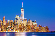 Freedom Tower rises above the New York Skyline of Downtown Manhattan at dusk in the Financial District, New York City.