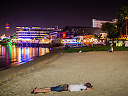"""26 SEPTEMBER 2014 - PATTAYA, CHONBURI, THAILAND: A tourist lies on the sand, passed out on Pataya Beach. Pataya, a beach resort about two hours from Bangkok, has wrestled with a reputation of having a high crime rate and being a haven for sex tourism. After the coup in May, the military government cracked down on other Thai beach resorts, notably Phuket and Hua Hin, putting military officers in charge of law enforcement and cleaning up unlicensed businesses that encroached on beaches. Pattaya city officials have launched their own crackdown and clean up in order to prevent a military crackdown. City officials have vowed to remake Pattaya as a """"family friendly"""" destination. City police and tourist police now patrol """"Walking Street,"""" Pattaya's notorious red light district, and officials are cracking down on unlicensed businesses on the beach.     PHOTO BY JACK KURTZ"""