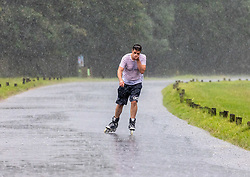 Licensed to London News Pictures. 12/07/2021. London, UK. A rollerblader gets caught in torrential rain in Richmond Park, southwest London this afternoon with roads and pavements becoming quickly flooded as the Met Office issue yellow weather warnings for heavy rain and thunderstorms which may cause disruption to travel and flooding. However, sunshine and warm weather is predicted for the rest of the week with highs of 26c for the weekend.. Photo credit: Alex Lentati/LNP