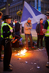 © Licensed to London News Pictures. 19/09/2014. Glasgow, UK. Disappointed 'Yes' voters and campaigners reacting to Scotland's decision to stay in the union by burning a copy of The Sun newspaper at George Square in Glasgow on Friday, 19 September 2014, after the Scottish independence referendum. Photo credit : Tolga Akmen/LNP