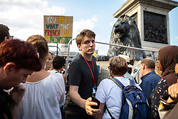 © Licensed to London News Pictures . 13/07/2018. London, UK. Momentum's JAMES SCHNEIDER amongst thousands of demonstrators in Trafalgar Square at a rally in protest against US President Donald Trump's UK visit . Photo credit: Joel Goodman/LNP