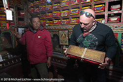 Scotty Busch holding a precious Buddhist manuscript in a private family museum in Marpha on day-6 of our Himalayan Heroes adventure riding from Muktinath to Tatopani, Nepal. Sunday, November 11, 2018. Photography ©2018 Michael Lichter.