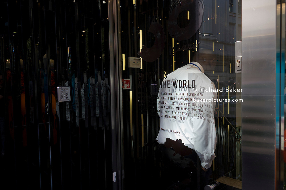 A security guard stands discreetly near the exit of a branch of the clothing brand Karen Millen in central London. Karen Millen is an Icelandic owned women's designer clothing brand, specialising in tailoring, coats and eveningwear. Karen Millen stores are found throughout the United Kingdom, America, Austria, Denmark, the Republic of Ireland and many other European countries.