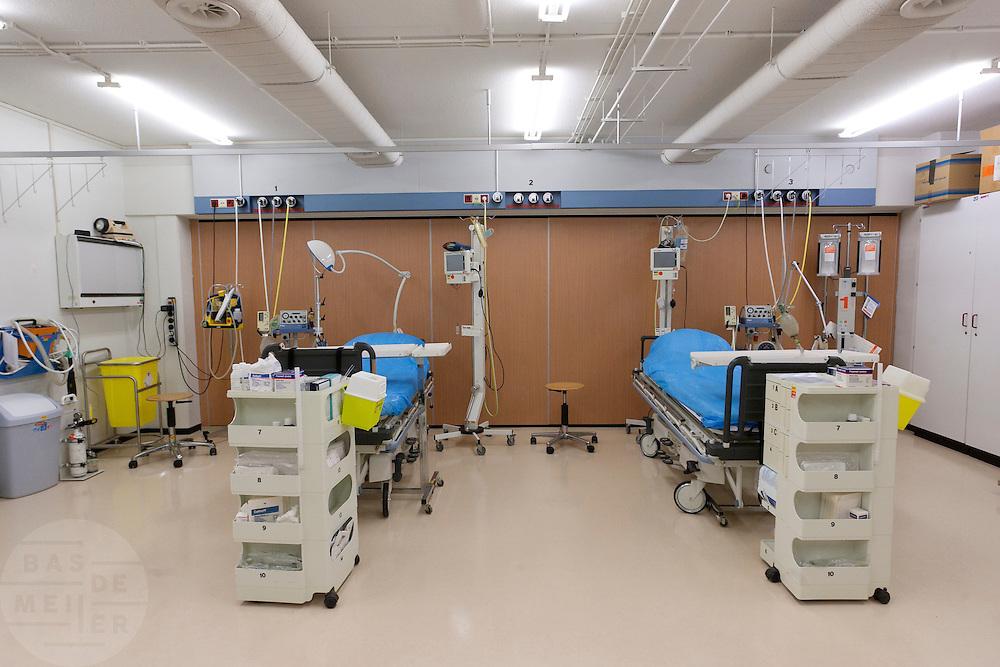 De rode sluis, waar de slachtoffers met de ernstigste verwondingen worden behandeld, van het calamiteitenhospitaal. Binnen een half uur moet de patiënt naar een vervolgafdeling zijn vervoerd. De naam van het slachtoffer is nog niet van belang, bij binnenkomst wordt hij voorzien van een nummer. Bij het calamiteitenhospitaal in Utrecht worden slachtoffers van grote rampen als eerste behandeld. Afhankelijk van de ernst van de verwonding, wordt het slachtoffer ingedeeld in rood, geel of groen. Het hospitaal is uniek in Europa en is gevestigd in de voormalige atoombunker onder het UMC Utrecht. <br /> <br /> The red zone of the trauma and emergency hospital, for the patients with the worst injuries. At the basement of the UMC Utrecht a special hospital for emergency and major incidents is based. Patients are being labelled by number and depending on the injuries they will be transported to the zone red, yellow or green.