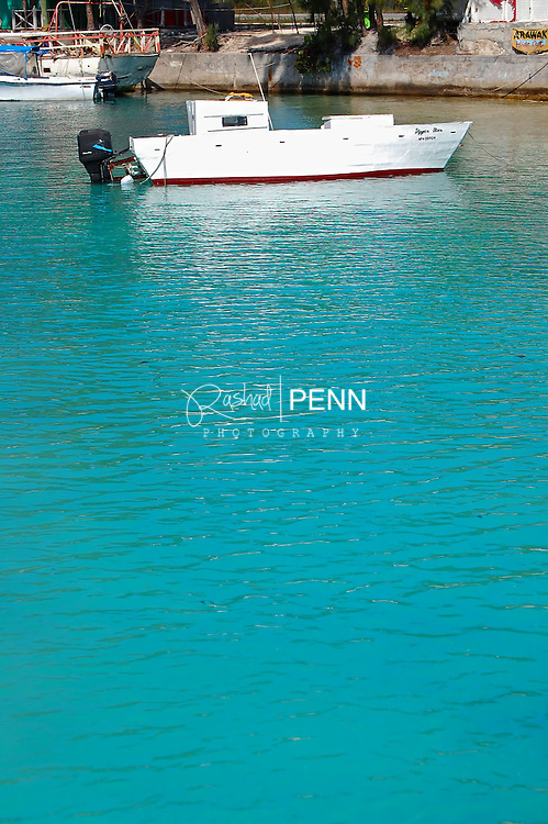 White Bahamian fisherman boat on turquoise waters. Anchored in the harbour.
