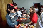 Teen serving Christmas dinner at church soup kitchen.  Minneapolis Minnesota USA