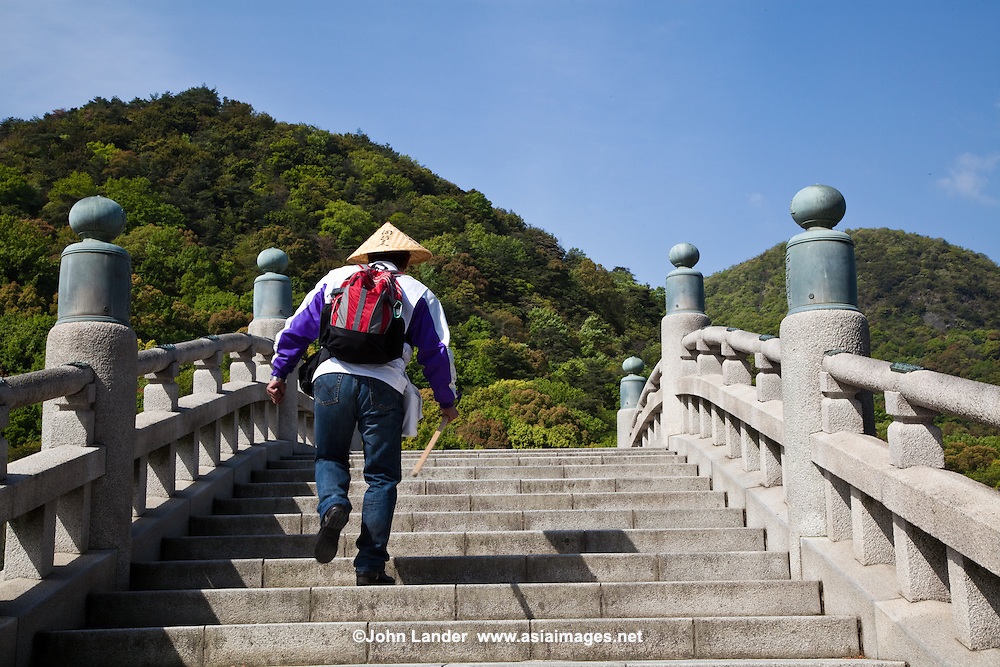 """The Shikoku Pilgrimage is a trail of 88 temples.  It is believed all these temples were visited by the famous Buddhist monk Kukai, founder of the Shingon school. The pilgrimage has long been completed on foot, but modern pilgrims take public transporation or even bicycles or motorcycles. The walking course is approximately 1200 kilometers long and can take up to 60 days to complete. """"Henro"""" is the Japanese word for pilgrim - they are recognisable by their white clothing, sedge hats, and walking sticks."""