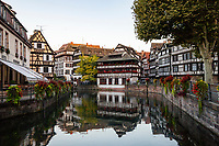 Half-Timbered Architecture at La Petite France Strasbourg - La Petite France lies west of the Grand Île or Strasbourg town center.  The area is a lovely place to visiton foot or even by boat. This historic area is surrounded by water, the River Ill and canals. Many historic half-timbered homes are along the shores of the river and canals. HistoricallyLa Petite Francewas once a poor part of town, occupied by mills and tanneries, both of which depended on the river and its downward flow. The area also served as a port, transporting Alsatian goods such as wine. For many years it was an unsavoury place, until the middle of the 20th century when it was transformed into a charming tourist destination Most of the 16th and 17th century houses have been preserved and restored reflecting beautifully on the water.  Many of these buildings have been converted into cafes and restaurants, and the tanneries and port business are industries of the past.