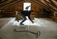 Martin Carney slides ice blocks to Ian Adams as they fill the 9th out of 10 rows of the Rockywald Ice House on Thursday afternoon.  (Karen Bobotas/for the Laconia Daily Sun)