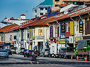 11 DECEMBER 2018 - SINGAPORE:  A woman crosses Sims Road in the Geylang neighborhood. Sims Road has many preserved Singapore shophouses. The Geylang area of Singapore, between the Central Business District and Changi Airport, was originally coconut plantations and Malay villages. During Singapore's boom the coconut plantations and other farms were pushed out and now the area is a working class community of Malay, Indian and Chinese people. In the 2000s, developers started gentrifying Geylang and new housing estate developments were built.    PHOTO BY JACK KURTZ