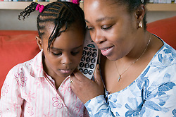 Young girl and mother sharing the phone to listen into a conversation,