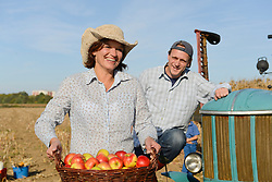 Farmer couple with tractor and basket of apples, Bavaria, Germany
