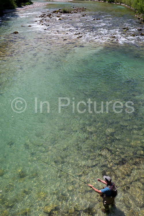 A fly-fisherman casts off in clear waters of the Sava Bohinjnka river, on 18th June 2018, in Bohinjska Bela, Bled, Slovenia.
