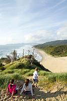 Family playing on sand dune in Pacific City, OR