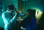 Doctor uses a fiberoptic scope to look up patient's nose.