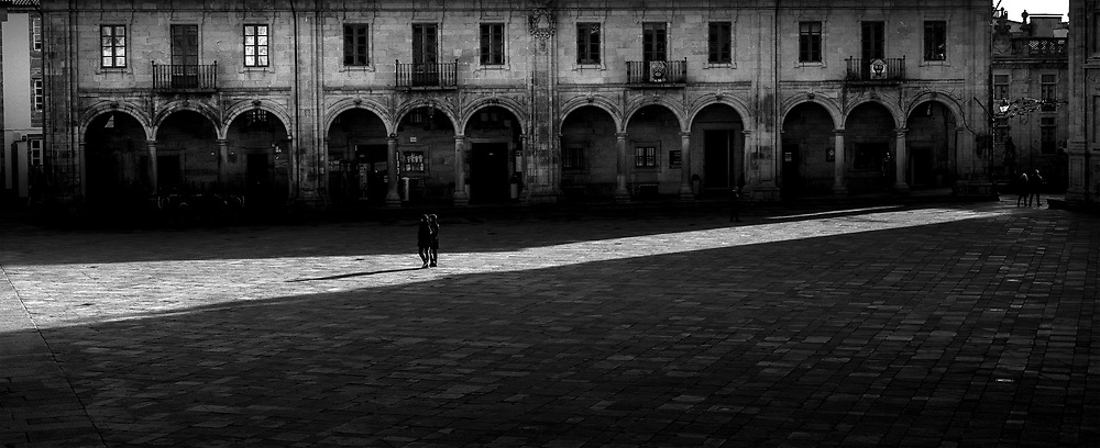 LAte afternoon light shines across a square in the old town of Santiago de Compestela.
