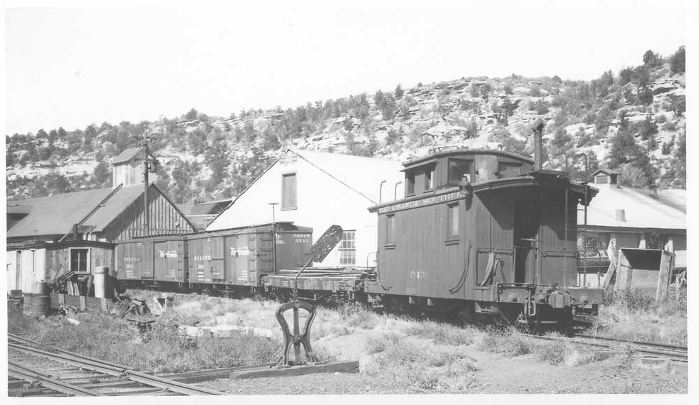 "RGS Dolores yards with two box cars, a flat and a caboose.  Section car shed and feed elevator are in background.<br /> RGS  Dolores, CO  Taken by Richardson, Robert W. - 10/10/1945<br /> In book ""RGS Story, The Vol. VII: Dolores and McPhee"" page 163<br /> Buildings were identified from page 61 of ""RGS Story, The Vol. VIII: Over the Bridges? Dolores to Mancos.""<br /> Same image as RD142-138."
