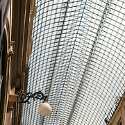 The distinctive glass domed roof of the Galeries St-Hubert in the Lower Town of Brussels, Belgium. Opened in 1847, St-Hubert was the first shopping arcade in Europe. It contains luxury shops and cafes and is made up of three smaller galleries: Galerie du Roi, Galerie de la Reine, and Galerie des Princes.