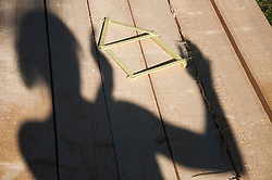 Shadow of person on wood besides folding ruler