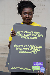 London, UK. 23rd March, 2019. An activist holds a placard referencing an increase in hate crimes since the European Referendum before the People's Vote march through central London from Park Lane to a rally in Parliament Square addressed by a selection of politicians and entertainers.