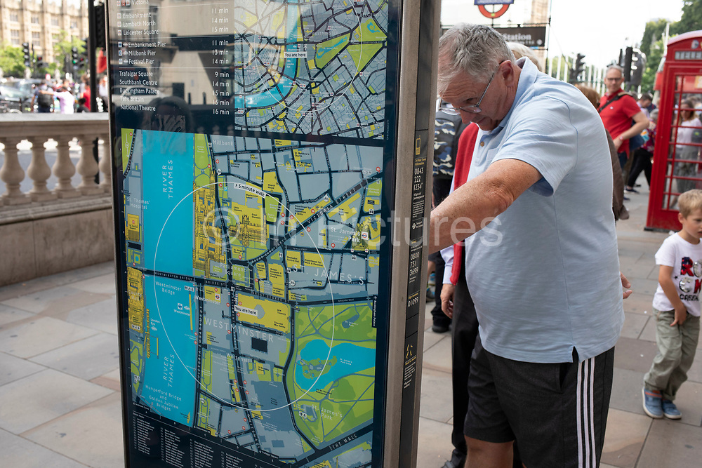 Tourist closely reading a public information map of central London, United Kingdom.