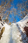 "Sun shines on frozen waterfall over sandstone outcrop ""Ķiparu kaskāde"" on snowy winter day, Gauja National Park (Gaujas Nacionālais parks), Latvia Ⓒ Davis Ulands | davisulands.com"